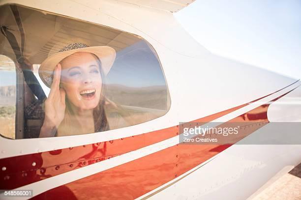 Tourist waving from inside plane