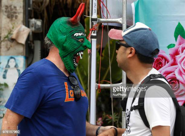A tourist wear a mask representing the spirits of the dead springing back to life during the annual Phi Ta Khon or Ghost festival in Dan Sai Loei...