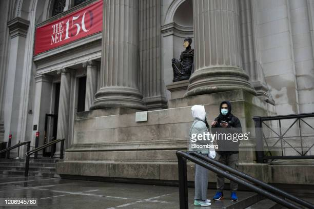 Tourist wear protective masks while standing in front of the Metropolitan Museum of Art while closed in New York, U.S., on Friday, March 13, 2020....