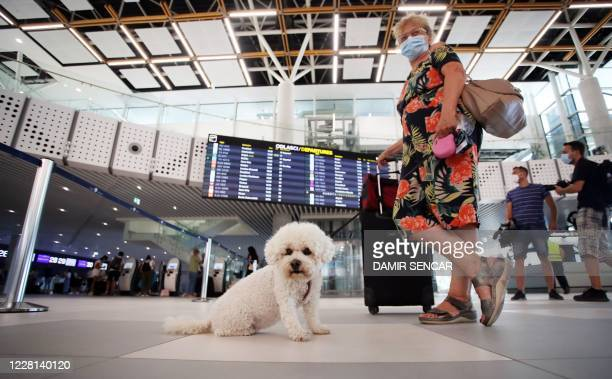 A tourist wearing a face mask waits at Split International Airport in Split Croatia on August 21 2020 As United Kingdom removed Croatia from the list...