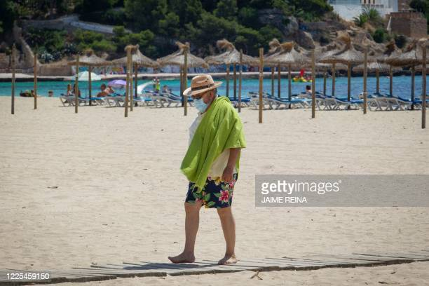A tourist wearing a face mask walks on Magaluf Beach in Calvia on the Spanish island of Mallorca on July 8 2020 The Balearic Islands are expecting a...