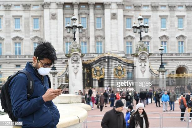 Tourist wearing a mask checks his cellphone in front of Buckingham Palace in London on March 14, 2020. - British Prime Minister Boris Johnson, who...
