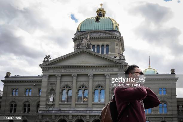 Tourist wearing a mask is seen in front of the Swiss House of Parliament on March 13 in Bern ahead of the announcement by Swiss government of new...
