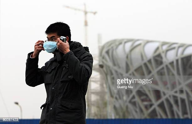 Tourist wearing a mask stands in front of the Olympic Stadium known as the 'Birds Nest ' which is shrouded with smog on March 18, 2008 in Beijing,...