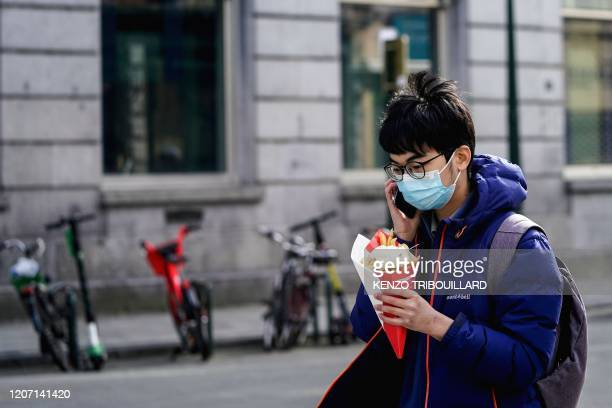 A tourist wearing a protective face mask walks as he holds a French fries cornet in the centre of Brussels on March 14 amid the outbreak of COVID19...