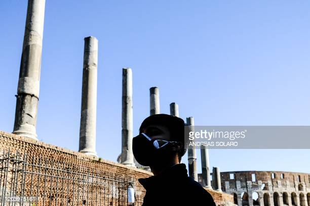 A tourist wearing a protective respiratory mask tours outside Palatino hill near the Coliseum in downtown Rome on February 28 after COVID19 the novel...