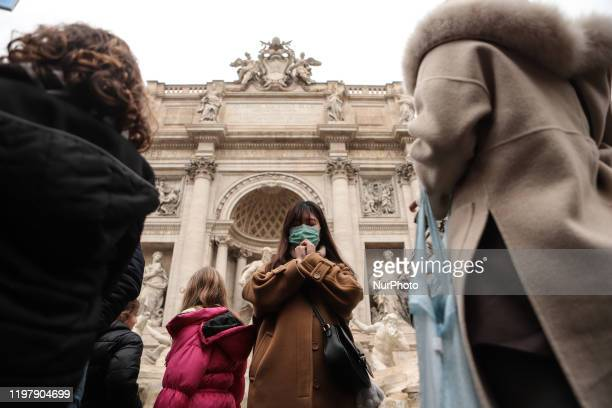 Tourist wearing a protective respiratory mask tours outside the Fontana di Trevi monument in downtown Rome on February, 2020