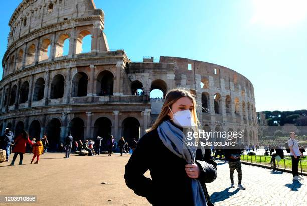 Tourist wearing a protective respiratory mask tours outside the Colosseo monument in downtown Rome on February 28 2020 amid fear of Covid19 epidemic...