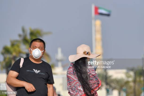 A Tourist wearing a surgical mask is pictured next to Burj in Dubai on January 29 2020 The United Arab Emirates announced the first confirmed cases...