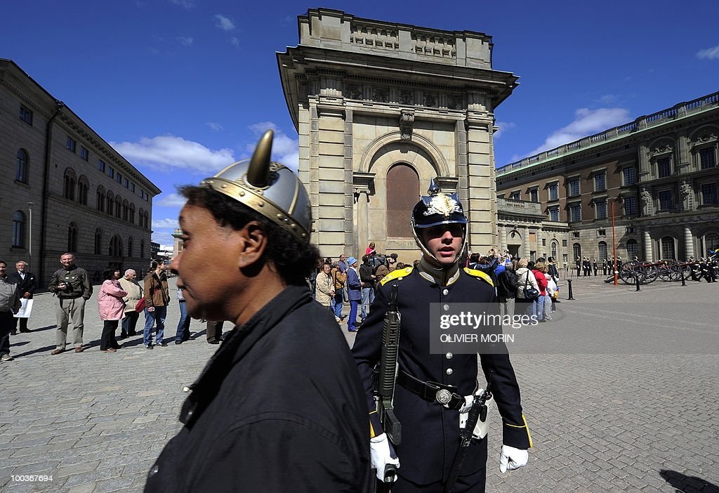 A tourist wearing a toy Viking helmet passes by a royal guard in front of the Royal Palace in Stockholm on May 24,2010. Many tourists paid a visit to the Swedish capital less than a month before Crown Princess Victoria 's wedding, the 32-year-old eldest daughter of King Carl XVI Gustaf.