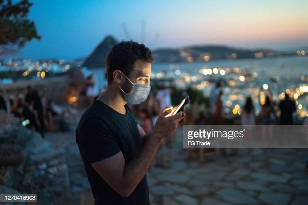 tourist wearing face mask using smartphone - greece tourism stock pictures, royalty-free photos & images