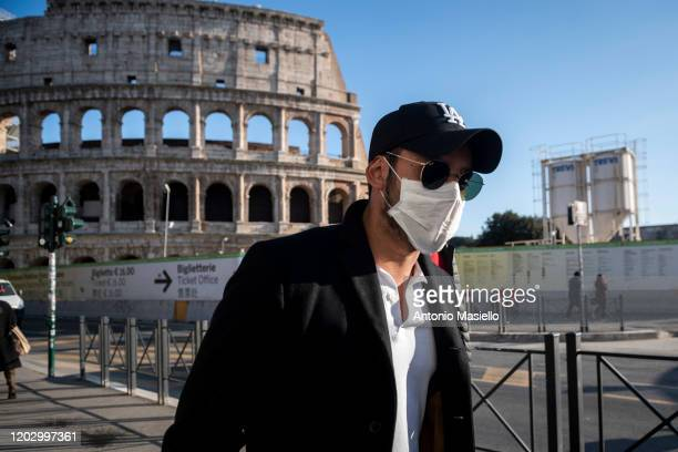 Tourist wearing face masks visits the Colosseum area on February 24, 2020 in Rome, Italy. The Italian government declared a state of emergency on...