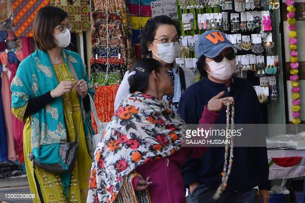 Tourist wearing facemasks as a preventative measure against the COVID-19 coronavirus, walk along a market area in New Delhi on February 12, 2020. -...