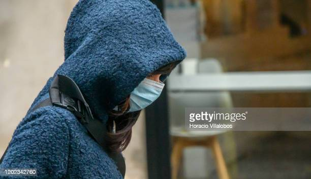 A tourist wears a disposable face mask to prevent contagion while walking in LX Factory complex on January 27 2020 in Lisbon Portugal Portuguese...
