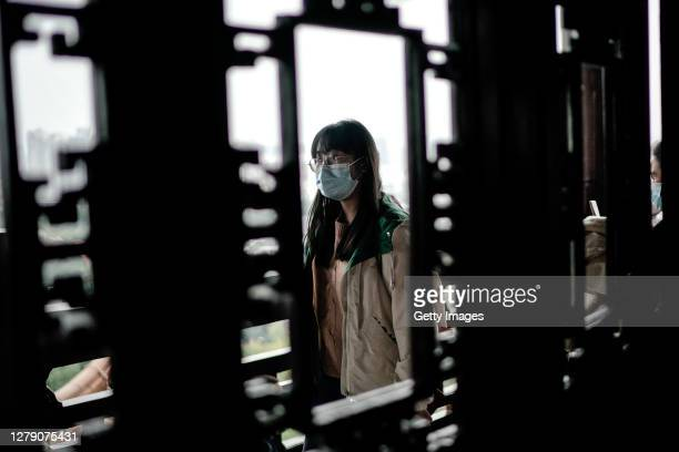 A tourist wears a mask while visiting the Yellow Crane Tower on October 7 2020 in Wuhan Hubei province China China is celebrating its national day...