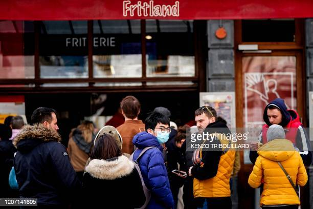 A tourist wears a protective face mask as he lines up in front of a French fries shop near the GrandPlace in the centre of Brussels on March 14 amid...