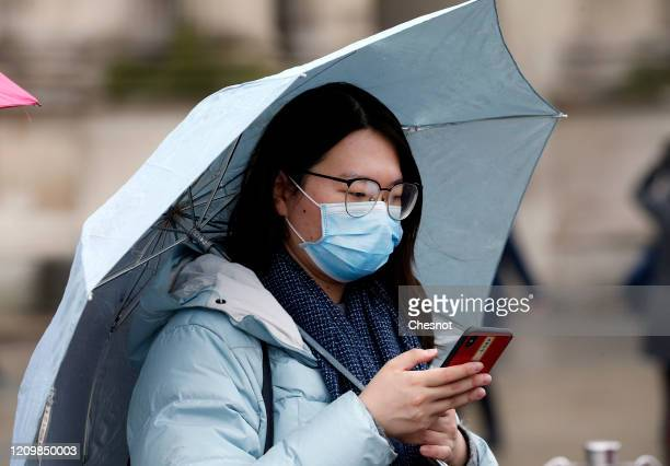 A tourist wears a protective mask in front of the Louvre Museum as the museum was closed for a staff meeting about the coronavirus outbreak on March...
