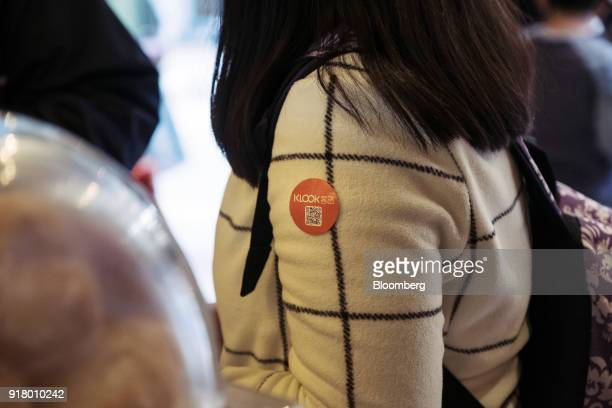 A tourist wears a sticker displaying a quick response code during a guided walking tour hosted by Klook Travel Technology Ltd in Hong Kong China on...