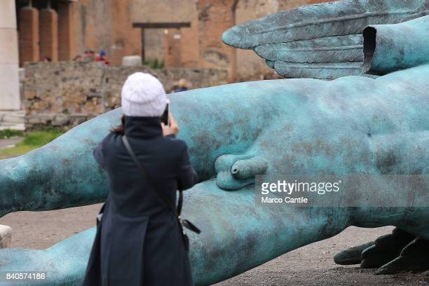 A tourist while taking pictures of the penis of one of the great statues of Mitoraj in the excavations of Pompeii in the Forum the main square of the...
