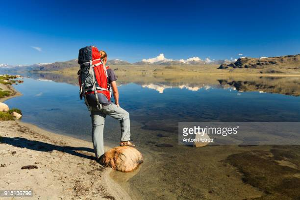 Tourist with a backpack and mountain lake view