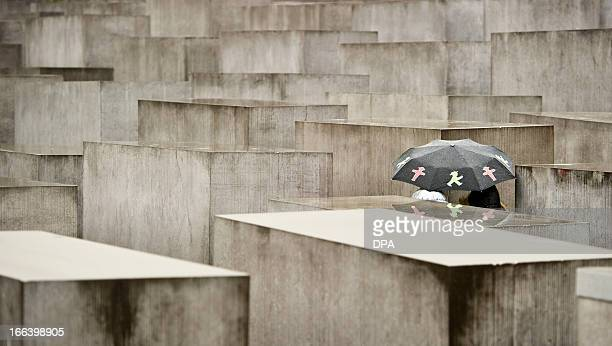 A tourist with an umbrella decorated with former East Germany's famous Ampelmaennchen walks past concrete steles of the Monument for the Murdered...