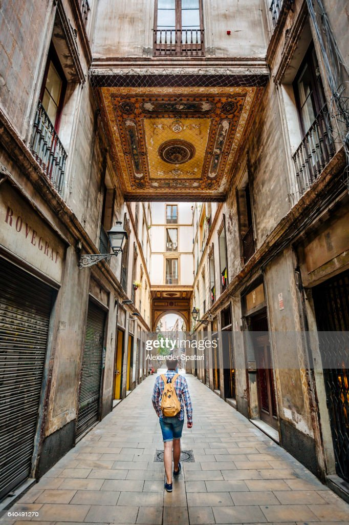 Tourist with backpack bag wandering through the narrow street of Gothic Quarter in Barcelona, Catalonia, Spain : Stock Photo