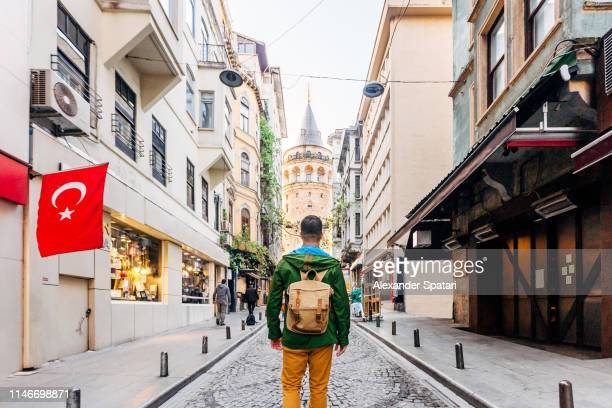 tourist with backpack looking at galata tower, istanbul, turkey - turquie photos et images de collection