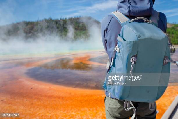 Tourist with backpack on Grand Prismatic Spring with puffy clouds overhead in Yellowstone National Park, Wyoming.
