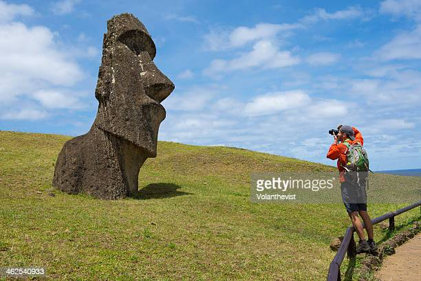 Tourist with backpack shooting a moai in Rapa Nui