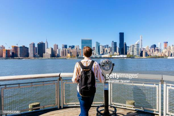 Tourist with backpack standing next to coin operated binocular and looking at New York City skyline