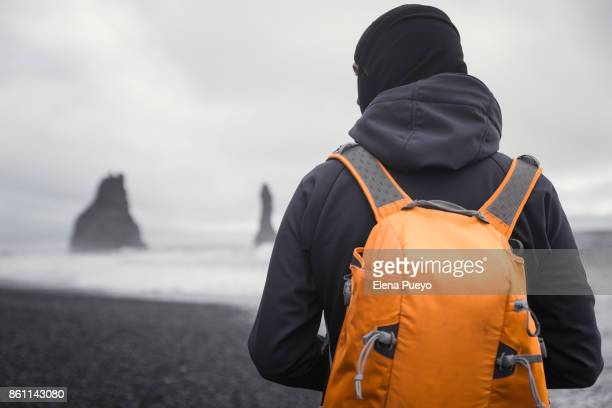 Tourist with backpack taking photos on The Sea Stack Rocks at Vik in Iceland, black beach