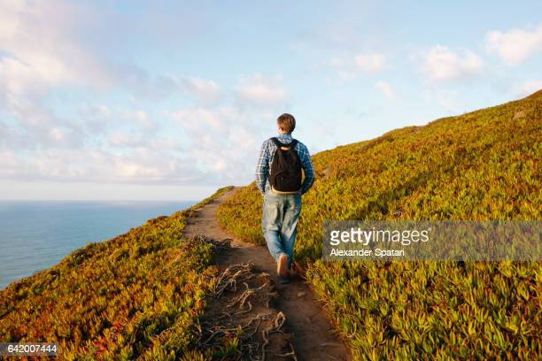 Tourist with backpack walking on a hiking trail along the ocean