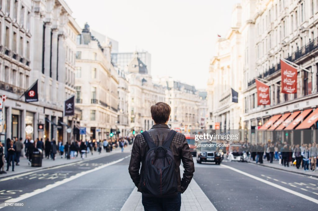 Tourist with backpack walking on Regent Street in London, UK : Stock Photo