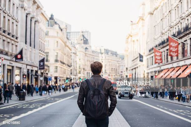 tourist with backpack walking on regent street in london, uk - high street stock pictures, royalty-free photos & images