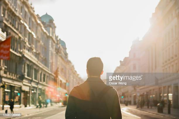 tourist with backpack walking on the street in london at sunset - day stock pictures, royalty-free photos & images