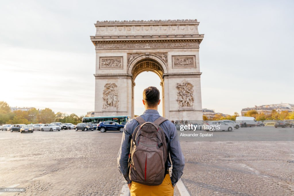 Tourist with backpack walking towards Arc de Triomphe in Paris, France : Stock Photo