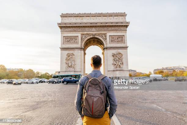tourist with backpack walking towards arc de triomphe in paris, france - wereldreis stockfoto's en -beelden