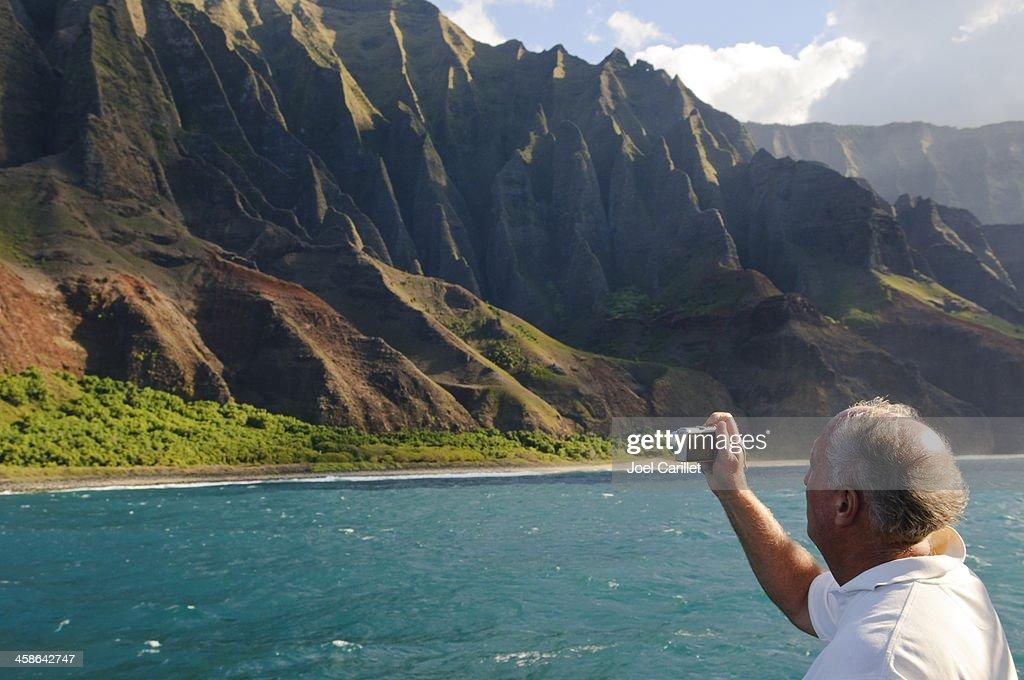 Tourist with camera in Hawaii's Na Pali Coast : Stock Photo