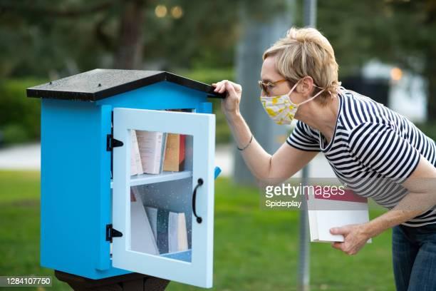 フェイスマスクを持つ観光客無料シェアライブラリから本を選択 - 1 minute 50 ストックフォトと画像
