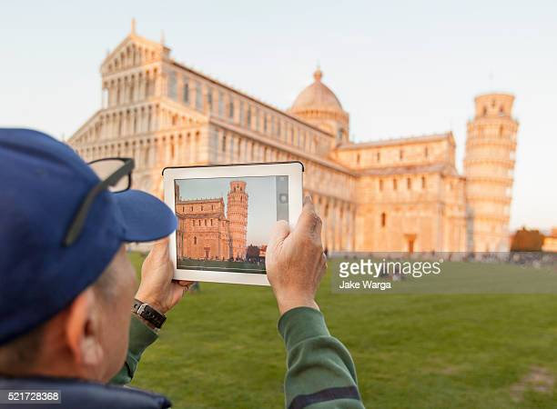 tourist with ipad photographing the leaning tower of pisa, sunset - apple computers stock pictures, royalty-free photos & images