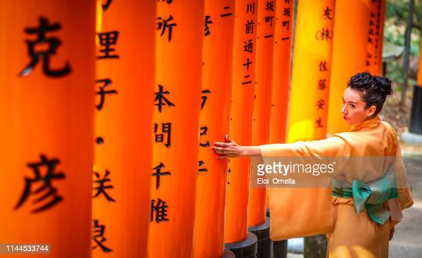 tourist with kimono touching a torii in fushimi inari taisha, kyoto, japan - kyoto prefecture stock pictures, royalty-free photos & images