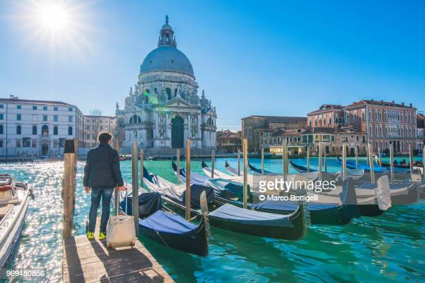 tourist with luggage trolley walking in venice, italy - canale grande venedig stock-fotos und bilder