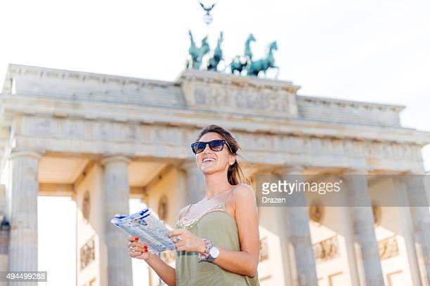 Tourist with map finding landmarks near Brandenburg Gate, Berlin