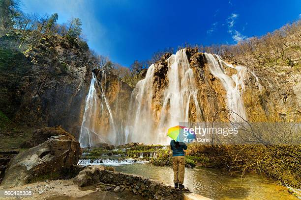 Tourist with rainbow umbrella at Plitvice Lakes