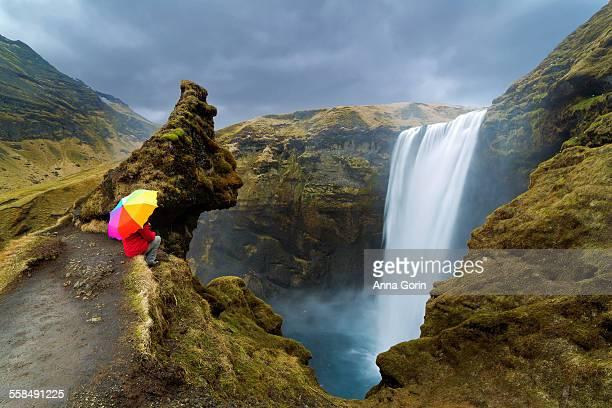 Tourist with rainbow umbrella sits by Skogafoss