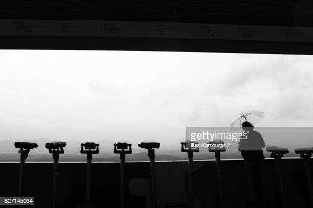 Tourist with umbrella at observation platform, North Korea in background