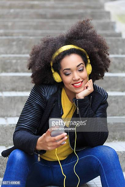 Tourist with yellow headphones listening music on stairs