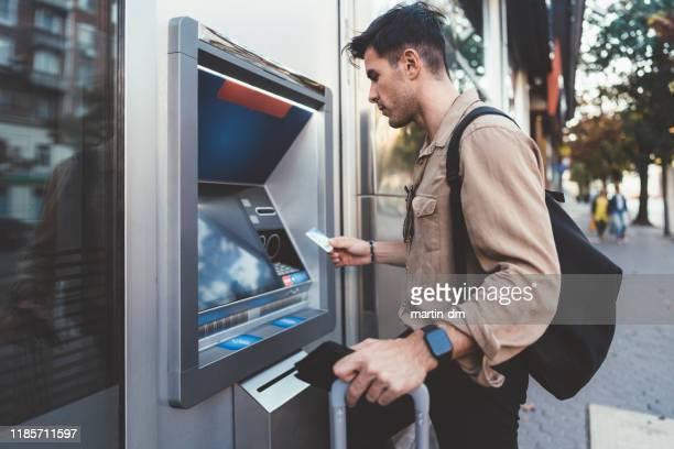 tourist zieht geld am geldautomaten ab - geldautomat stock-fotos und bilder
