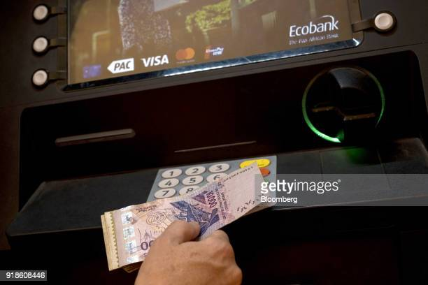 A tourist withdraws West African CFA franc currency banknotes from an automated teller machine outside an Ecobank Guinea Bissau bank branch in Bissau...