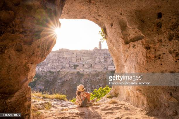 tourist woman admiring matera from a cave at sunset, basilicata, italy - basilicata region stock pictures, royalty-free photos & images